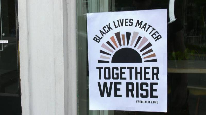 Together We Rise campaign poster hangs in business window in Charlottesville.