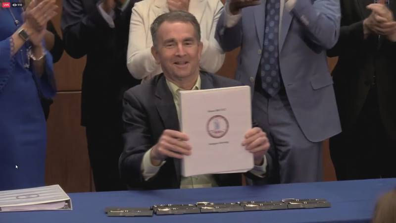 Governor Ralph Northam (D-Virginia) holds up the signed bill legalizing simple possession of...