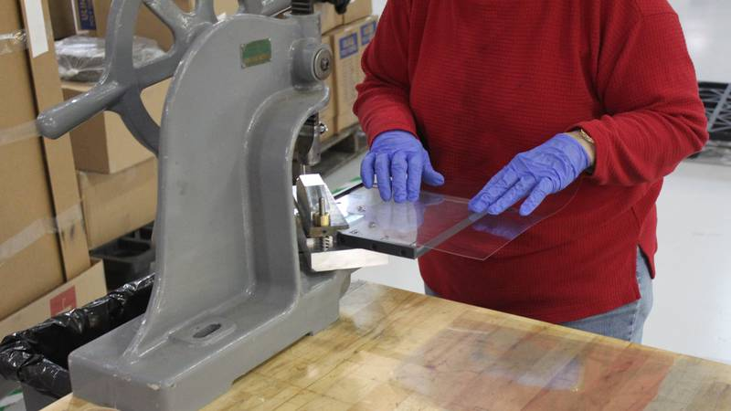 A staff member at MicroAire cutting plastic to help produce a face shield