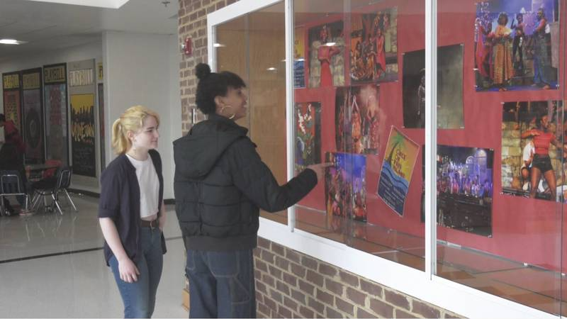 Kai Landers (left)  and Christiana Mitchell (right) look at photos of past theater productions...