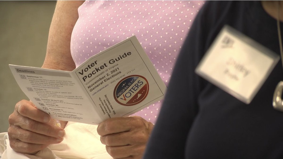 A woman reading a voter pocket guide at the voter security seminar.