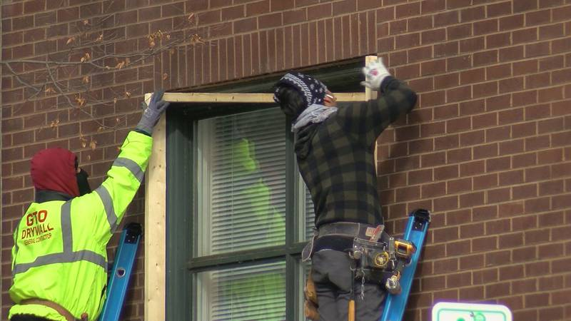 Contractors board up windows of buildings in Downtown Richmond, by Virginia State Capitol.