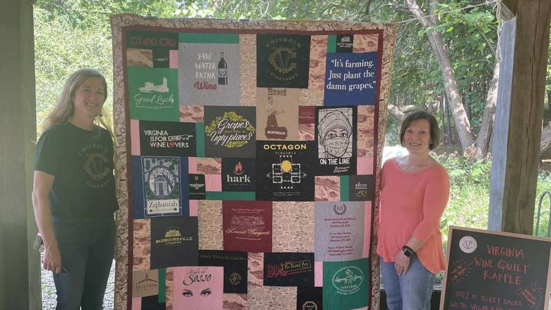 Andrea Matheson and Kim Payne standing with the quilt