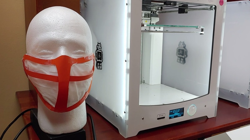 A University of Virginia professor is printing and cutting out face masks at home to help...