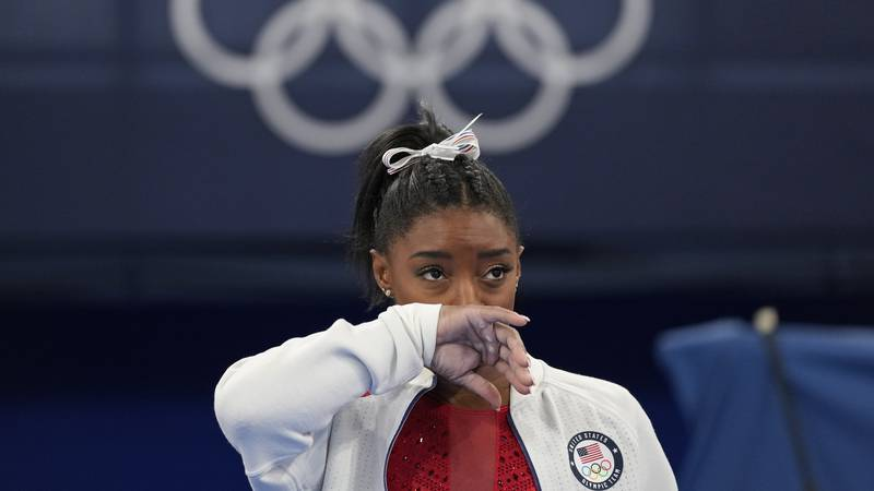 Simone Biles, of the United States, watches gymnasts perform at the 2020 Summer Olympics,...