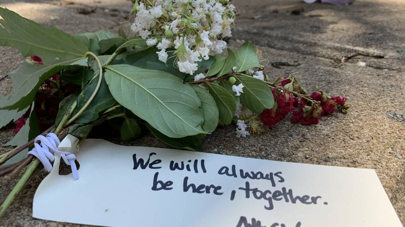A flower and note on the ground at Honorary Heather Heyer Way on August 12, 2020