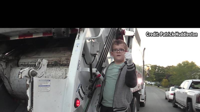 Luke Cox poses on the side of the trash truck that visits his neighborhood every week.