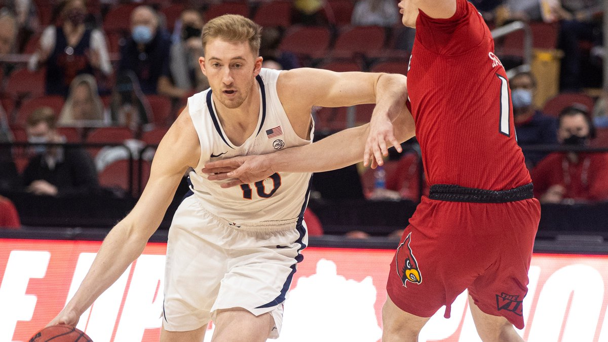 Virginia's Sam Hauser drives to the basket during the first half as the Louisville Cardinals...