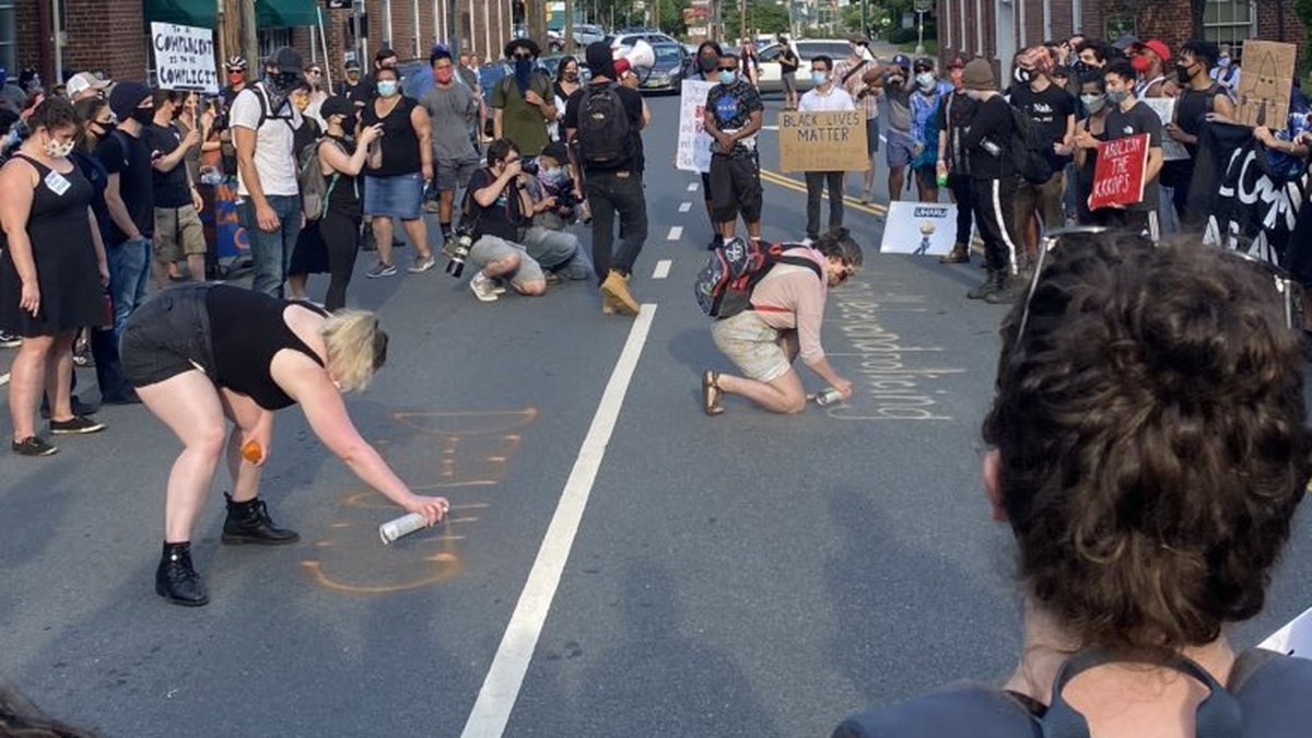 """""""DEFUND + ABOLISH"""" being spray painted on E. Market Street outside the Charlottesville Police..."""