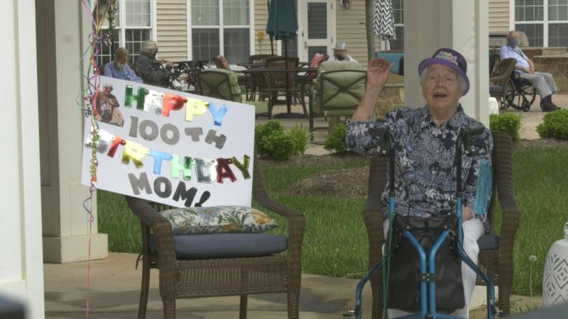 Virginia James waves to family and friends during a 100th birthday parade outside RoseWood...