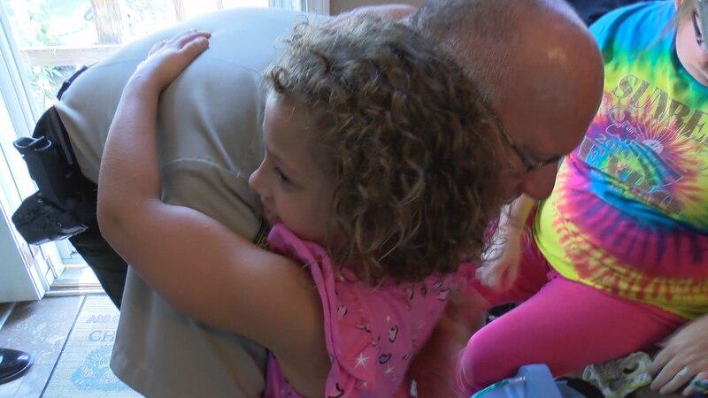 Sheriff Darrell Perkins gets a hug from 6-year-old Mylah Santa Maria Thursday.