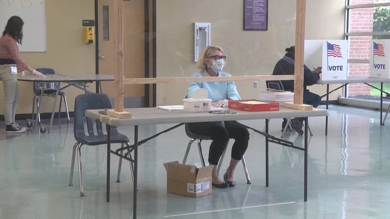 A poll official wears a mask and sits behind a shield separating workers from voters on...