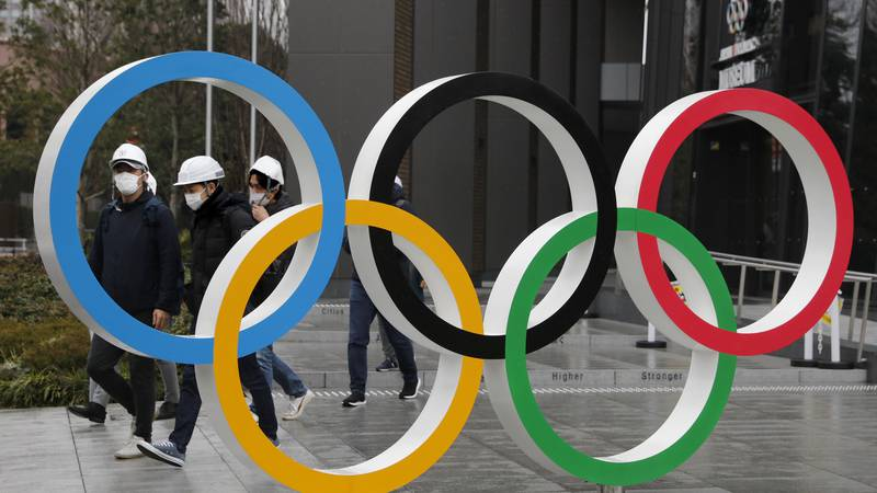 In this March 4, 2020, file photo, people wearing masks walk past the Olympic rings near the...
