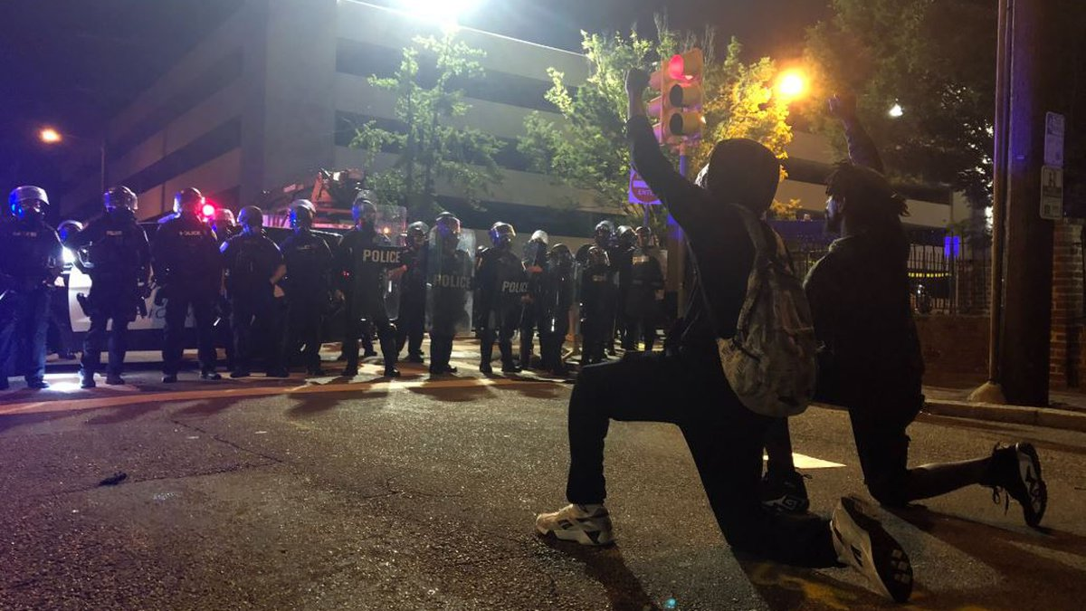 Two demonstrators kneel in front of dozens of police officers on Madison Street Richmond.