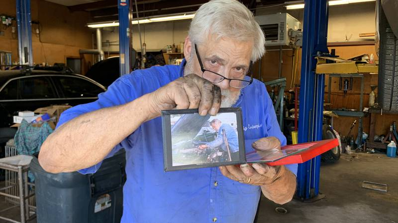 Harry Lynwood Craig Jr. holding a picture of himself under the hood.